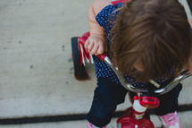 a toddler girl riding a red tricycle