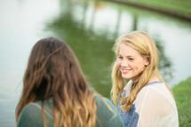 women talking in front of a lake