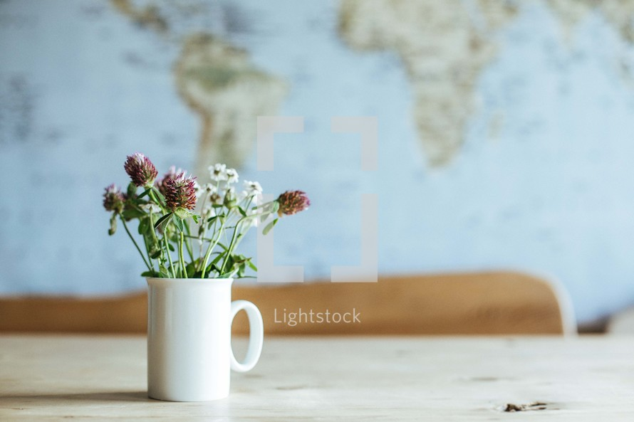 A cup full of wildflowers on a table.