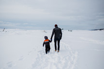 father and son walking through snow