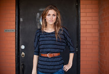 woman standing with her hand on her hip in front of a brick wall