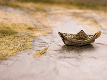 paper origami boat from the pages of a Bible on a world map