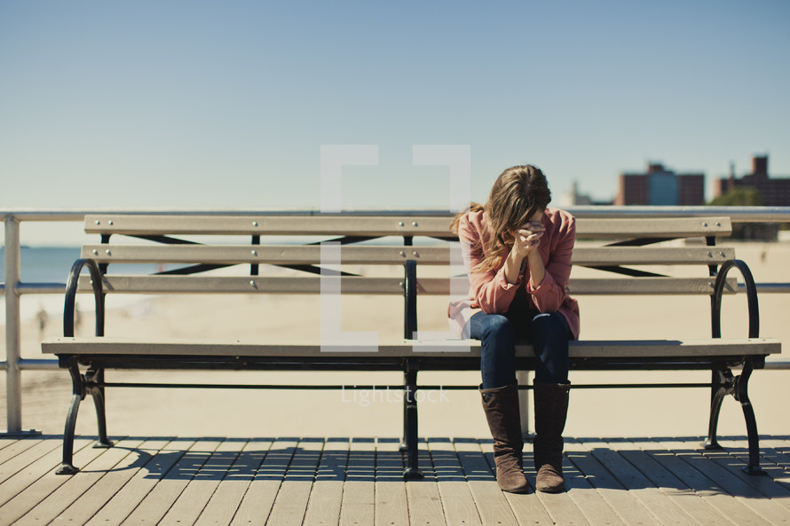 A young woman praying on a bench near Coney Island