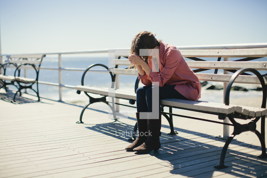 Woman sitting on bench on ocean side deck with elbows on her knees and her head resting on her folded hands.