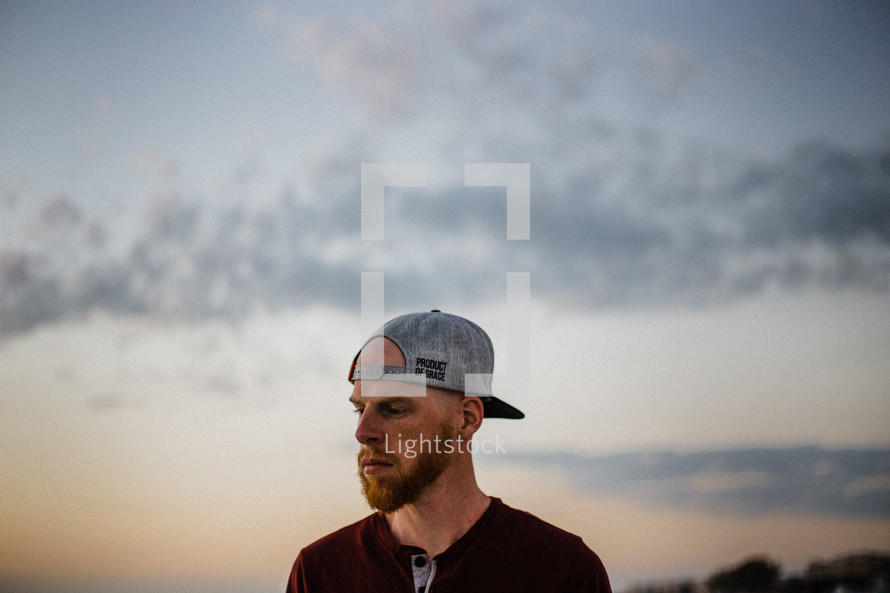 a man standing outdoors with a backwards ball cap