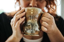a woman sipping from a mug