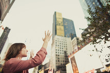 woman with hands raised in praise and worship in the city
