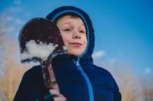 a child in with a shovel in the snow