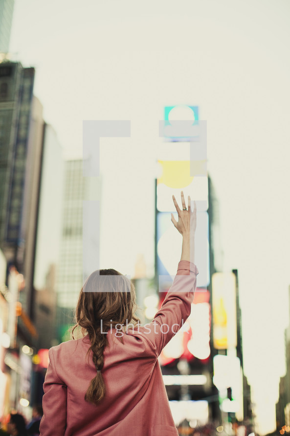 A young woman praying for the city in Times Square