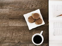 cookies on a napkin, coffee in a mug, and an open Bible