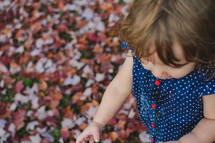 a toddler girl playing in fall leaves