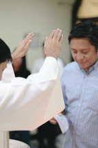 priest with raised hands by a baptismal font
