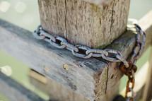 Rusty chain around fence post