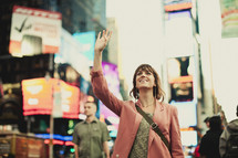 A young woman lifting her hand in Times Square