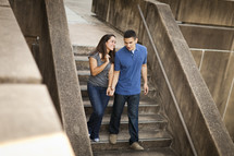Couple in jeans holding hands while walking down cement steps.