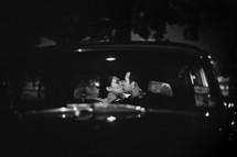 man and woman kissing in a car