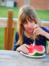 a girl child eating a watermelon
