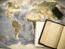 open Bible, journal, and cellphone on a map