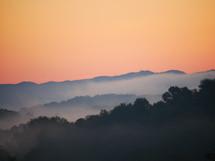 fog over a mountain at sunrise
