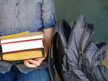 a student holding books near a book bag