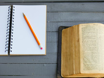 pencil on a journal and open Bible