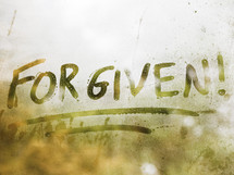 the word forgiven written on fogged glass