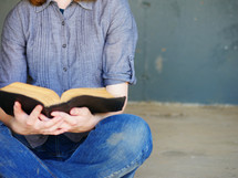 sitting reading a worn Bible