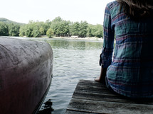 teen girl sitting on a pier on a lake beside a canoe