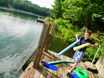 a boy child with pool noodles on a lake dock