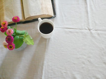 open Bible, vase of flowers, and coffee mug on a tablecloth