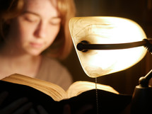 reading a Bible by the light of a desk lamp