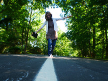 a teen girl walking on the center lines of a road holding a Bible
