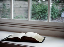 a Bible in a window sill