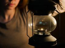 a woman holding a lantern