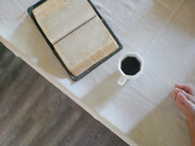 open Bible and coffee mug on a tablecloth