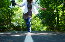 teen girl walking on the center lines of a road holding a Bible