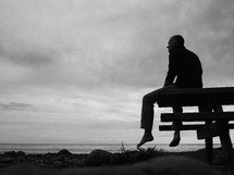 man sitting on a bench looking out at the ocean