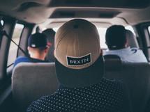hats turned backwards on men riding in a van