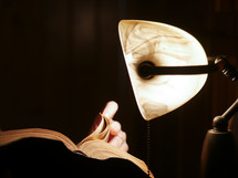 reading a Bible by light from a desk lamp