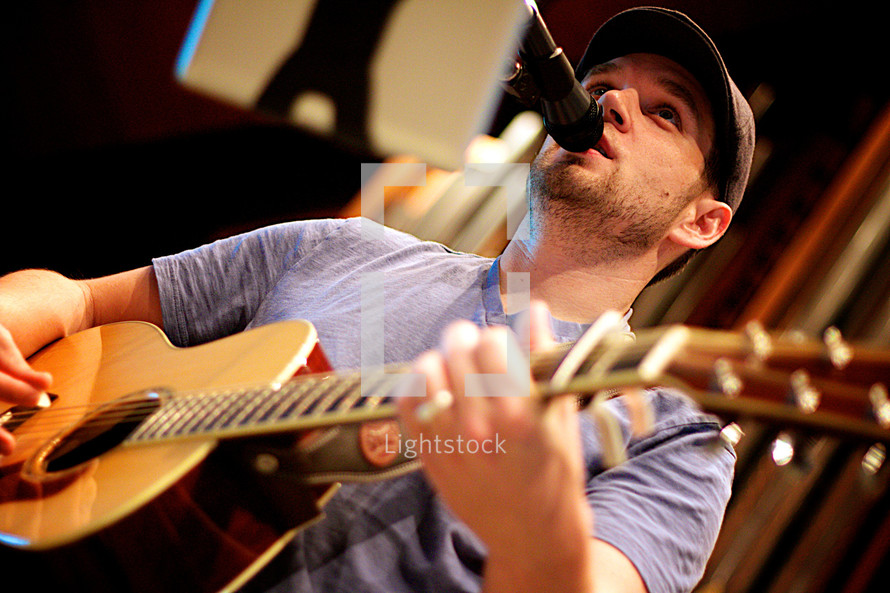 musician singing and playing a guitar