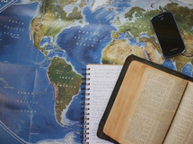 Bible, journal, and cellphone on a world map