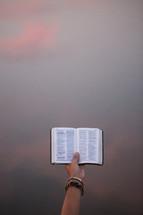a hand holding up a pocket Bible
