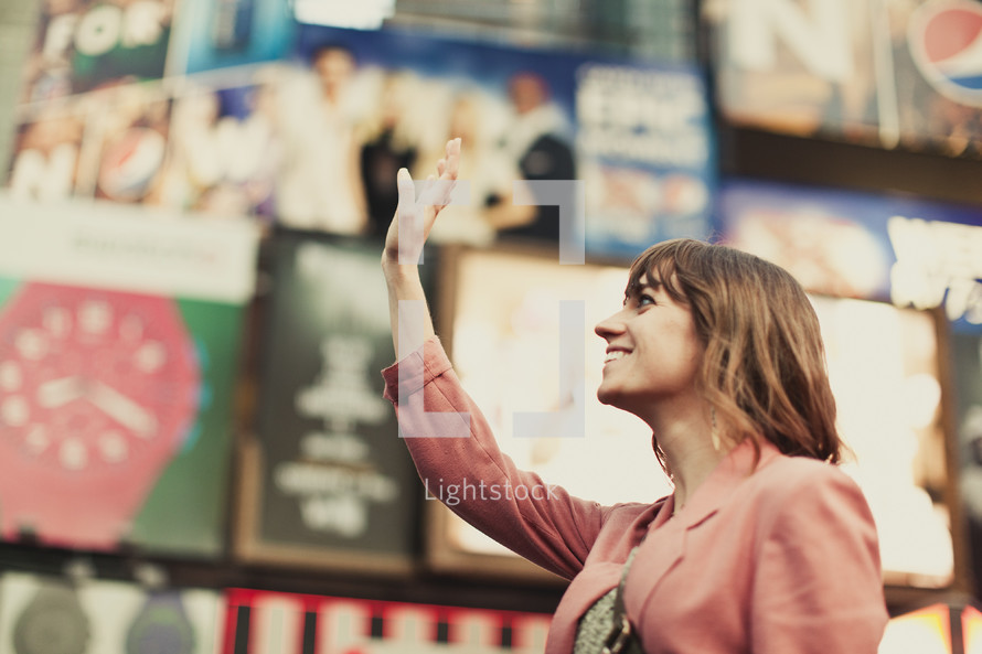 A young woman lifting her hand in Time Square