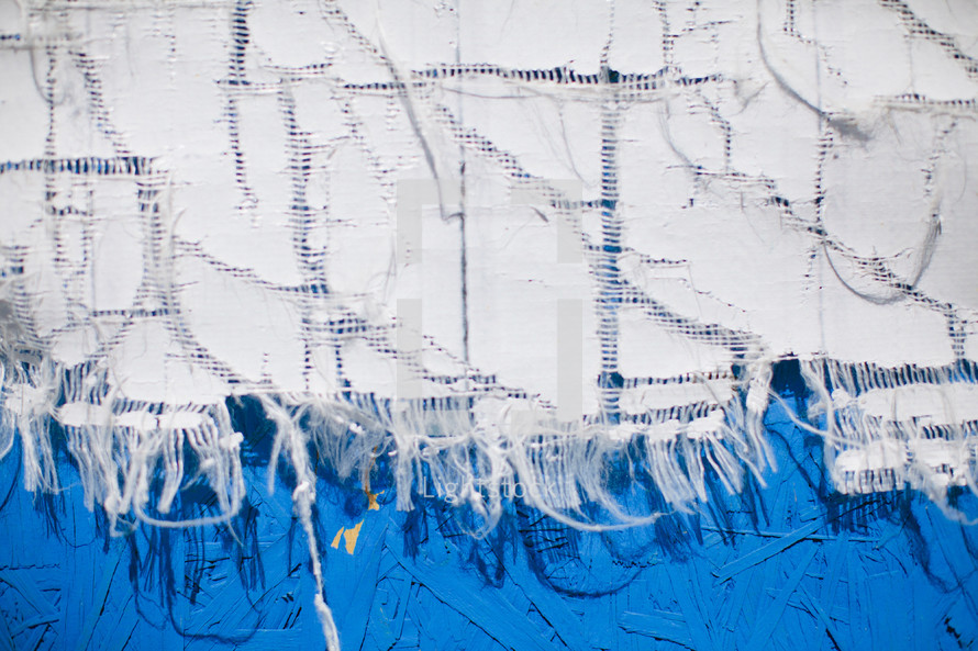Tattered tablecloth against blue wall