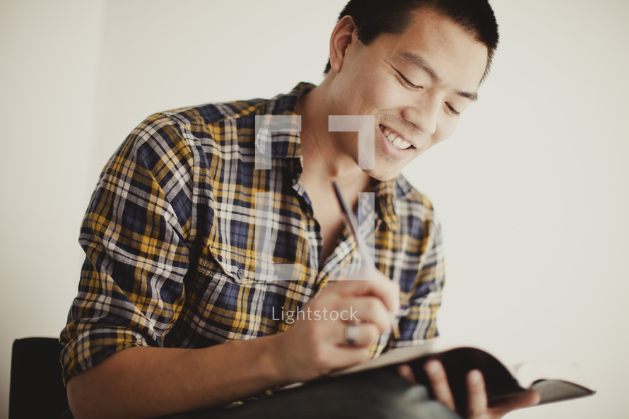 Man studying the BIble with a pen in hand