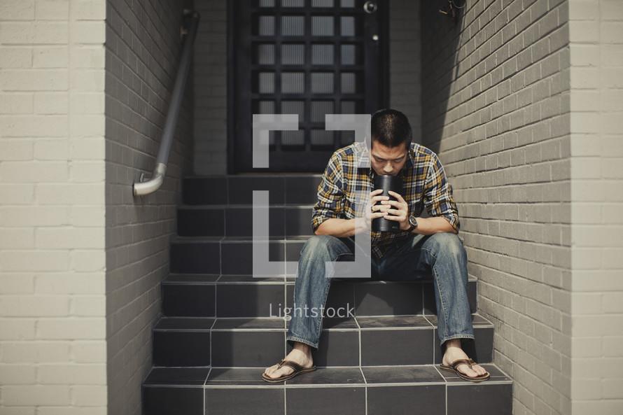 Man sitting on stairs praying