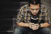 A man praying holding his BIble