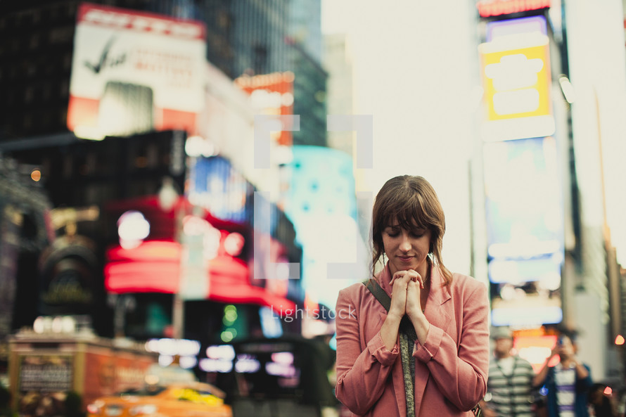 Woman praying in the city