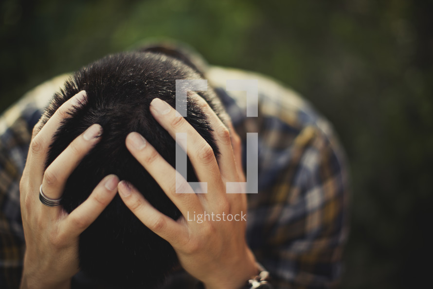 A man with his hands on his head