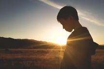 side profile of a boy child outdoors and a sunburst